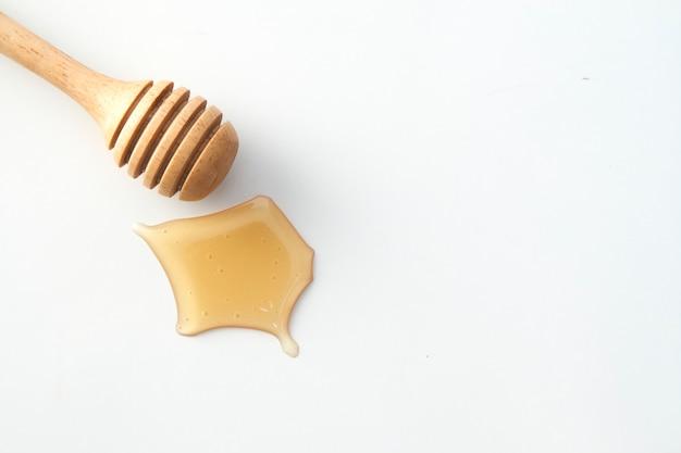 Bouteille de miel en bois et petite bouteille de miel sur blanc Photo Premium