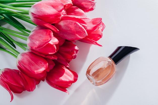 Bouteille de parfum aux tulipes roses. parfum floral. concept de cosmétiques naturels. cadeau pour femme Photo Premium