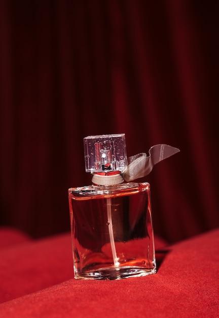 Une Bouteille De Parfum Féminin Sur Un Tissu De Velours Glamour Foncé Photo Premium