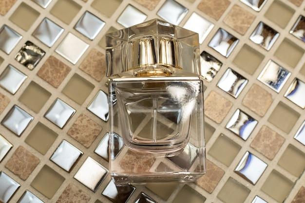 Bouteille De Parfum Sur Fond Doré Abstrait. Fermer Photo Premium