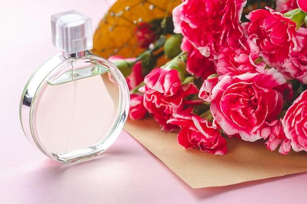 Une bouteille de parfum de personne et un bouquet de fleurs sur une surface rose. donnez des cadeaux et des fleurs à la personne. recevoir des cadeaux de personnes aimées en vacances Photo Premium