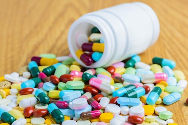 Bouteille pilule renverser pilules sur surface bois Photo Premium