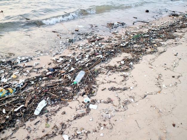 Bouteille en plastique bambou et déchets polluants sur la plage Photo Premium