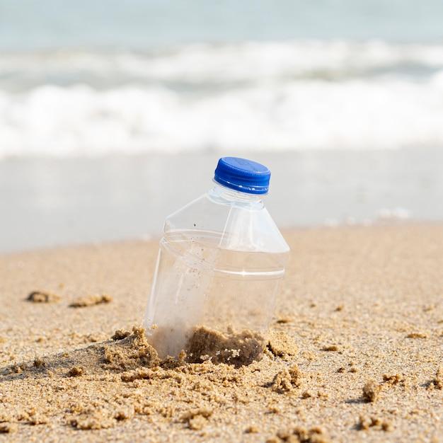 Bouteille en plastique laissée sur la plage Photo gratuit