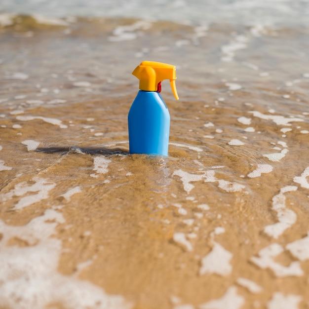 Bouteille en plastique de protection solaire bleue dans l'eau de mer peu profonde de la plage Photo gratuit