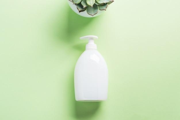 Bouteille de savon blanc naturel sur vert pastel Photo Premium