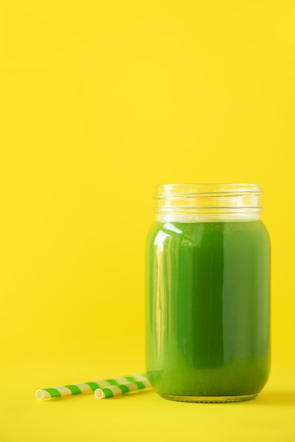 Bouteille de smoothie de céleri vert sur fond jaune Photo Premium