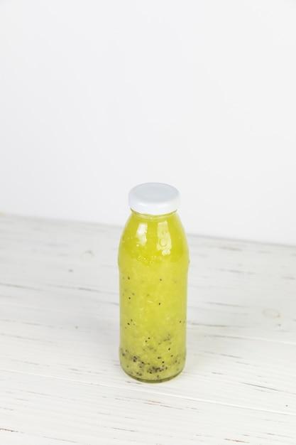 Bouteille de smoothie frais de brocoli fait maison sur une table blanche Photo gratuit