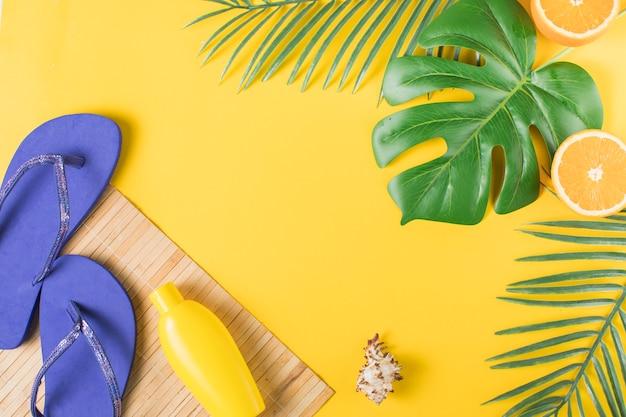 Bouteille avec des tongs sur tapis de paille et feuilles de la plante Photo gratuit