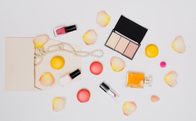 Bouteille de vernis à ongles; pétales de rose; collier; rouge à lèvres; macarons et bouteille de parfum isolé sur fond blanc Photo gratuit
