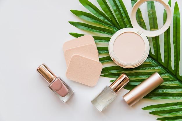 Bouteille de vernis à ongles; rouge à lèvres; éponge et compacte sur feuille verte sur fond blanc Photo gratuit