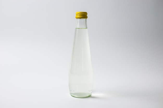 Bouteille en verre avec de l'eau sur fond isolé blanc Photo Premium