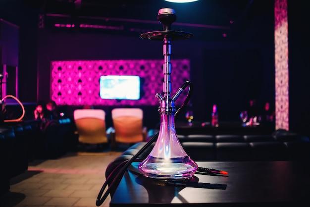 Bouteille en verre narguilé pour tabac à fumer dans les cafés sur le bureau Photo Premium