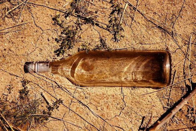 Bouteille en verre transparente sur le sol en terre battue en plein air, message écologique Photo Premium