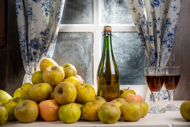 Bouteille et verres de cidre avec des pommes, près de la fenêtre, dans une maison rustique Photo Premium