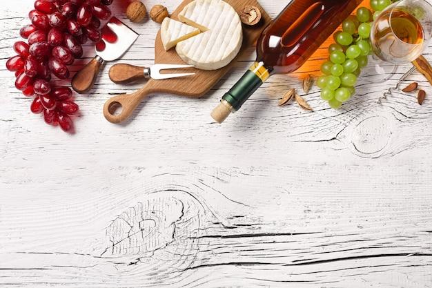 Bouteille de vin blanc, raisin, fromage et verre à vin sur une planche en bois blanche Photo Premium