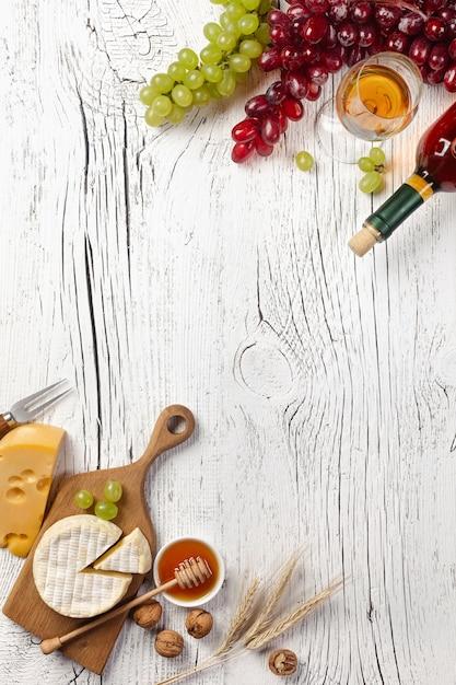 Bouteille de vin blanc, raisin, miel, fromage et verre à vin sur fond de planche de bois blanc Photo Premium