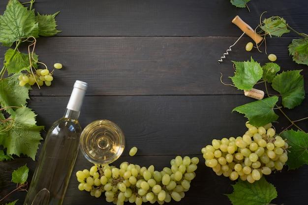 Bouteille De Vin Blanc Avec Verre à Vin, Bordure De Raisin Mûr Sur Table En Bois Photo Premium