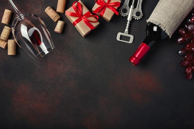Bouteille de vin, coffret cadeau, raisins rouges, tire-bouchon et bouchons en liège, sur fond rouillé Photo Premium