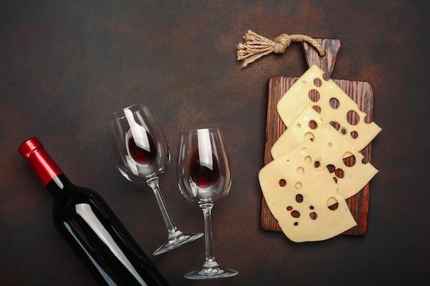Bouteille de vin, deux verres et du fromage maasdam tranchés sur une planche à découper sur fond rouillé Photo Premium