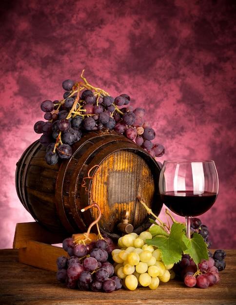 Bouteille de vin rouge et verre à vin sur tonneau Photo Premium