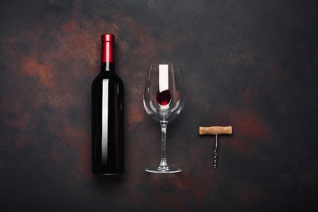 Bouteille de vin, tire-bouchon et verre à vin sur fond rouillé Photo Premium
