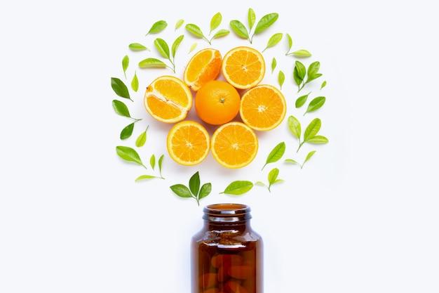 Bouteille de vitamine c et des pilules avec des fruits orange sur blanc Photo Premium