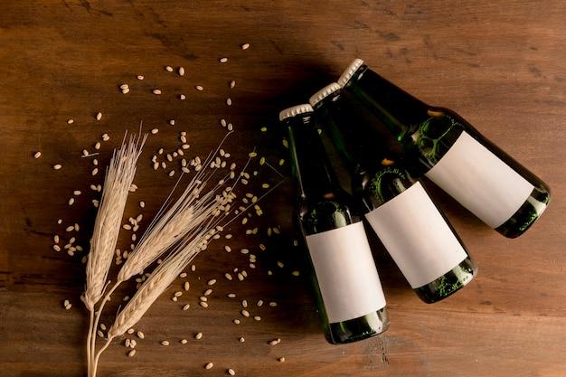 Bouteilles de bière en marque blanche avec épi de blé sur table en bois Photo gratuit