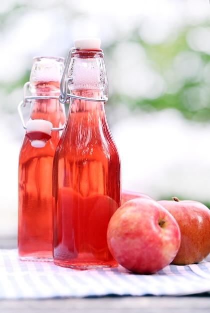 Bouteilles avec des boissons rouges et des pommes Photo gratuit