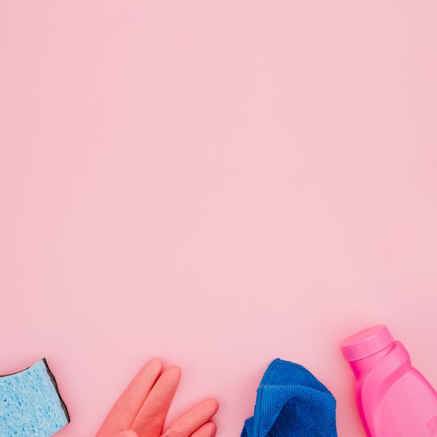 Bouteilles de détergent; gants; serviette bleue et éponges sur fond rose Photo gratuit