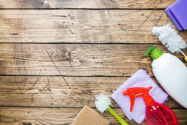 Bouteilles avec des détergents, des brosses et des éponges sur fond en bois. Photo Premium