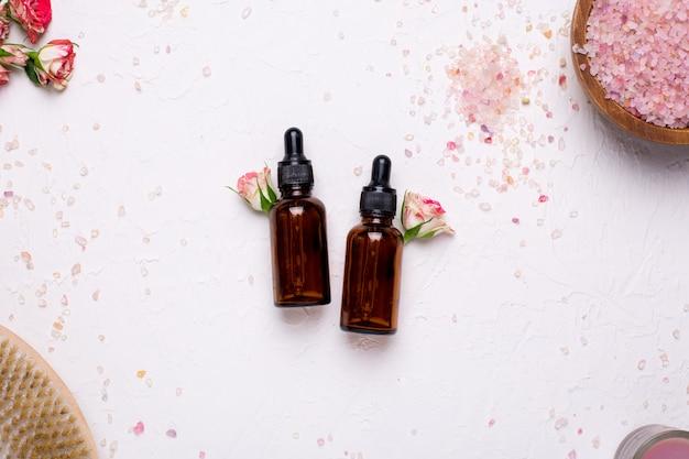 Bouteilles d'huile naturelles avec des fleurs et du sel de bain sur blanc Photo Premium