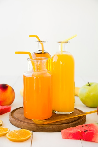 Bouteilles de jus d'orange avec paille sur un plateau en bois avec des fruits sur un bureau en bois Photo gratuit