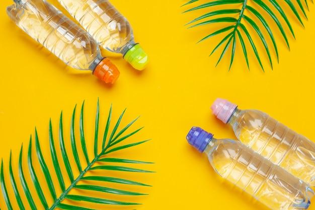 Bouteilles liquides transparentes avec des feuilles de palmier tropical Photo Premium