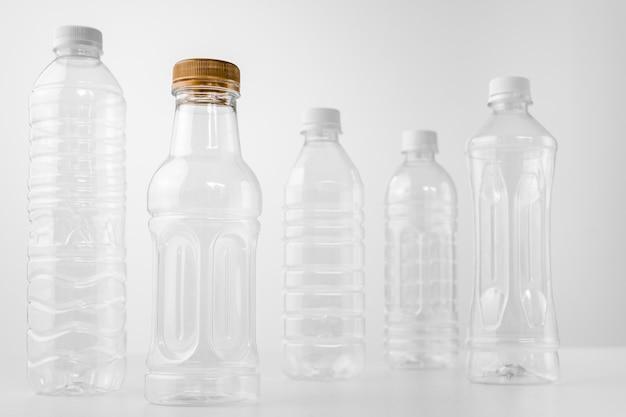 Bouteilles en plastique de différentes formes et tailles sur une table et un fond blancs Photo Premium