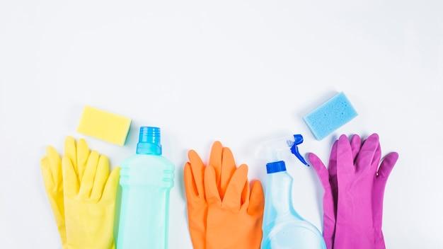 Bouteilles en plastique avec des gants et une éponge sur fond blanc Photo gratuit
