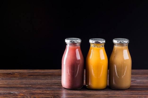 Bouteilles de smoothie sur une surface en bois Photo gratuit