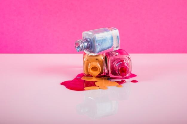 Bouteilles avec vernis à ongles renversé sur fond coloré Photo gratuit