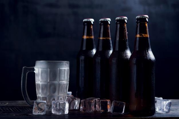 Bouteilles en verre de bière avec verre et glace sur fond sombre Photo gratuit