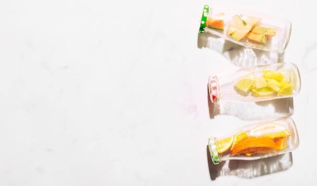 Bouteilles en verre avec des bouchons colorés pleins d'agrumes tranchés Photo gratuit