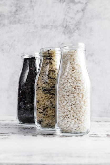 Bouteilles en verre avec différentes sortes de riz sur table Photo gratuit