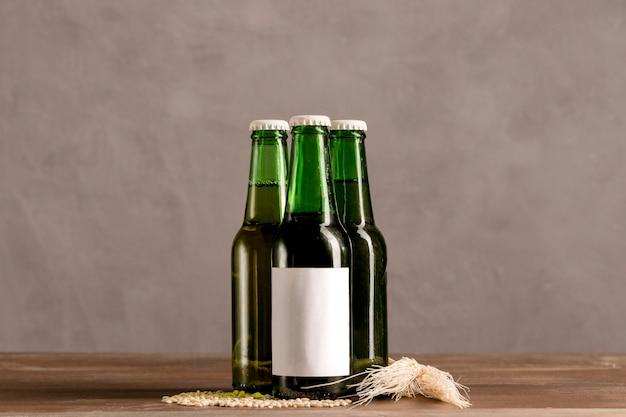 Bouteilles vertes en marque blanche sur une table en bois Photo gratuit