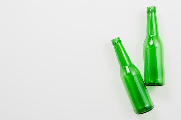 Bouteilles vides verts sur fond blanc Photo gratuit