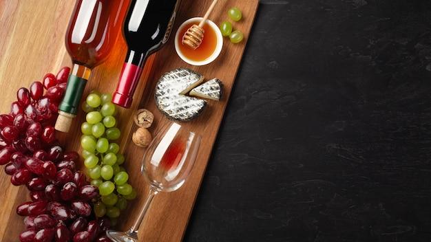 Bouteilles de vin rouges et blancs avec grappe de raisin, fromage, miel, noix et verre à vin sur bois Photo Premium