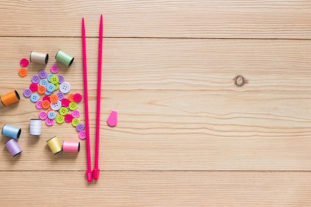 Bouton et bobine colorés avec des aiguilles à tricoter roses sur fond en bois Photo gratuit