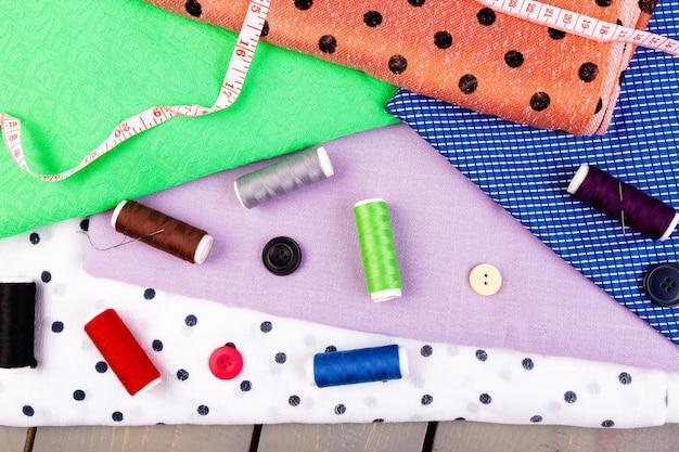 Boutons à coudre, bobines de fil et de tissu sur une table en bois Photo Premium