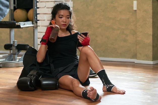 Boxer femme se détendre avec un smartphone après l'entraînement Photo gratuit