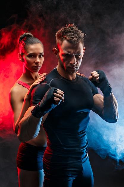 Boxer fort en position avec les poignets sur les poings avec sa petite amie derrière lui. Photo Premium