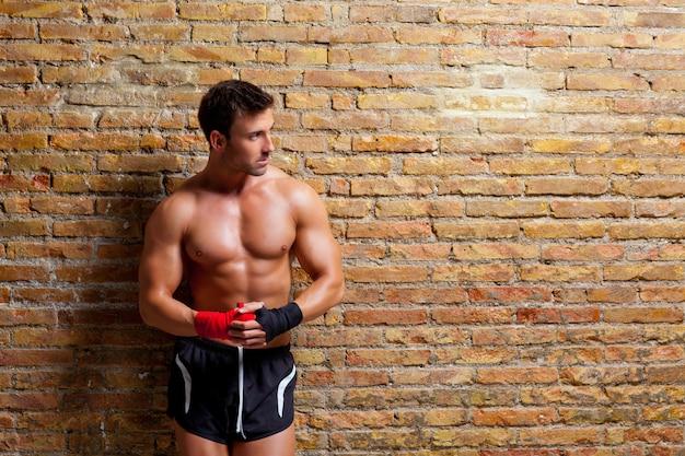Boxeur musculaire en forme d'homme avec un bandage de poing Photo Premium