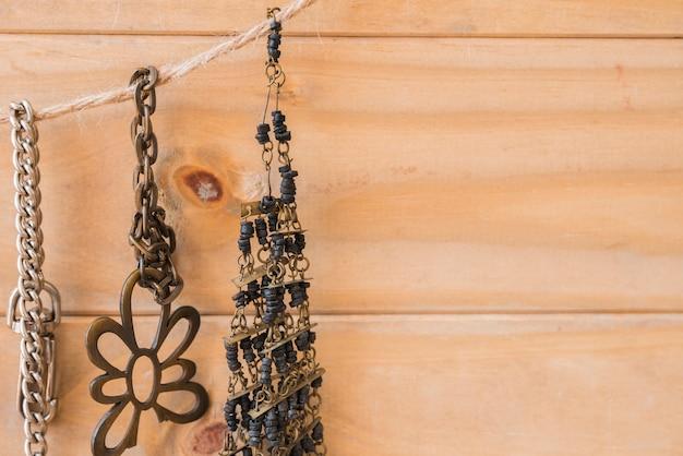 Bracelet métallique et perles ancien suspendu à une corde de jute contre un mur en bois Photo gratuit